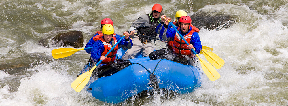 Four men with a guide whitewater rafting on Arkansas River in Buena Vista, Colorado.