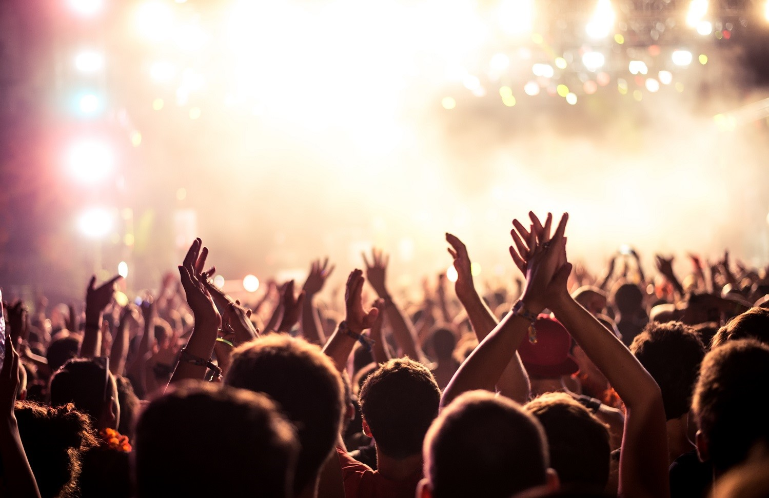Audience with hands raised at a music festival and lights streaming down from above the stage. Soft focus, blurred movement.