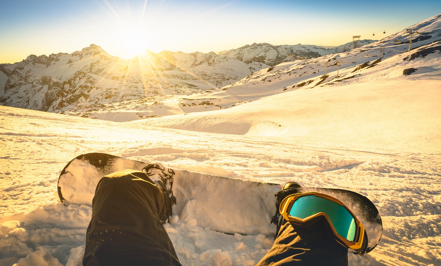 Snowboarder sitting on relax moment at sunset in public ski resort - Winter sport concept with person on top of the mountain ready to ride down