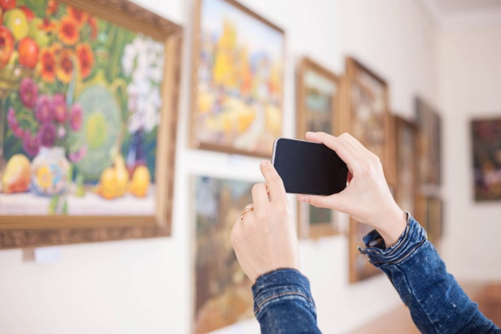 girl taking a picture of a painting at one of the best Aspen museums