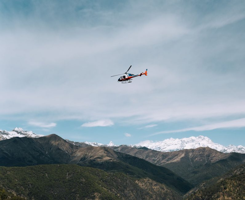 a helicopter flying around a mountain